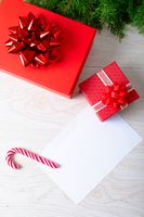 Composition of white card with copy space and fir tree branches with presents on wooden background