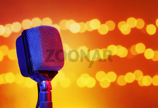 Music concept background with a vintage microphone in front of flashing lights. A transportation template with copy space for text