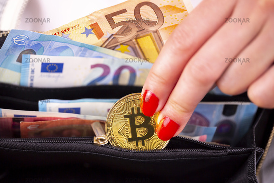 Bitcoin coins in woman's hand purse
