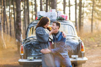Happy couple hugging and flirting standing near vintage car in woods