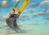 massive excavator bucket in front of cloudy sky