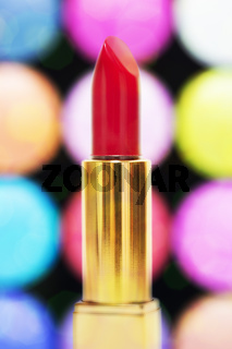 Red lipstick against colorful bokeh. Vertical shot.