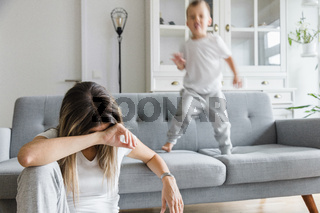 Hyperactive child and his tired and sad mother at home