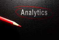 Analytics text circled in red pencil on dark textured surface