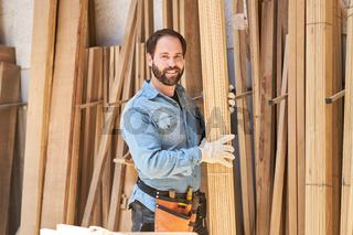 Schreiner trägt Bretter im Holzlager der Tischlerei