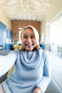 Happy senior caucasian woman in living room sitting on sofa, making video call