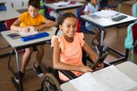 Portrait of disabled african american girl smiling while sitting on wheelchair at elementary school