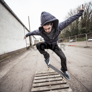 Skater doing ollie over wooden crate