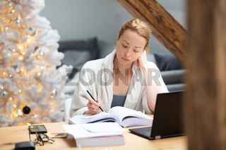 Young female entrepreneur wearing cosy warm bathrobe working remotly from home in winter Christmas time during 2020 corona virus pandemic. Work from home, selter in place, concept.
