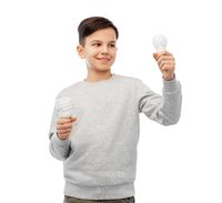 smiling boy comparing different light bulbs