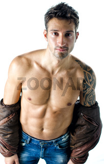 Handsome young man wearing leather jacket on naked torso