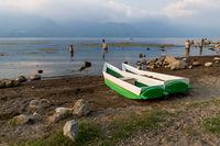 Two local fishermen canoes at the shore along lake Atitlan in San Pedro la Laguna, Guatemala