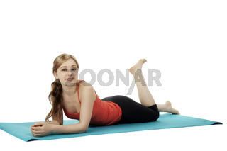 hübsche junge sportlerin liegt auf einer fitness matte