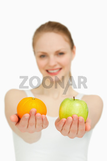 Close up of a young woman presenting fruits