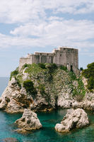 View from the wall of the old city of Dubrovnik on the fort Lovrijenac fortress on the cliff and the bay with a pier.