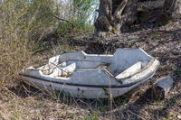 Old rotten paddle boat in the bushes