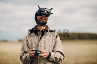 Man controlling fpv quadcopter drone with goggles antenna remote controller