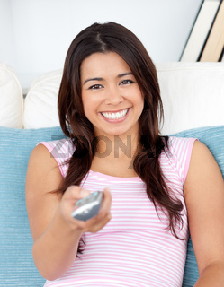 Captivating asian woman holding a remote smiling at the camera