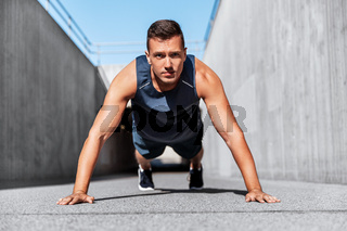 young man doing push ups on city street