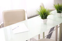 White glass office table with light beige artificial leather chair next to it