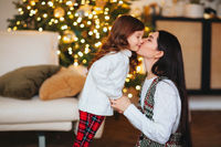 Beautiful loving mom gently kissing little daughter against festively decorated xmas tree at home
