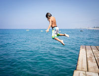 Little cute boy on sea pier enjoying summer