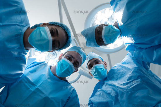 Diverse surgeons wearing face masks and protective clothing in operating theatre