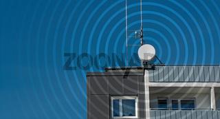 Sendemast auf Dach von Wohnhaus mit Funkwellen