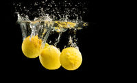 Fresh yellow lemons in water splash on black background