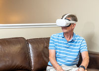 Senior adult man watching a game or movie on a modern VR headset