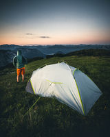 man in front of camping tent glow up with sunrise in morning in austria