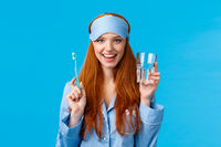 Advertising, hygiene and people concept. Feminine cute redhead girl feeling upbeat and enthusiastic start day right, drinking water, holding glass and toothbrush, wear nightwear and sleep mask