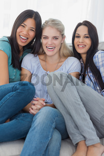 Friends laughing together and looking at camera