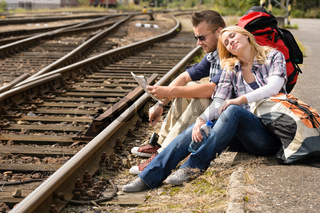 Couple resting looking at map railroad backpack
