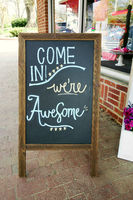Sandwich board sign in front of a small business with Come In We're Awesome message written in chalk