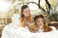 Mother and daughter with bunny resting on bed in garden