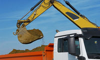 Excavator loads a trucks with excavation