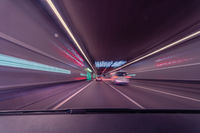 Drivers front view, driving fast in a tunnel by var with lots of blurry lights, concept for highspeed with a eyecatching violet tint.