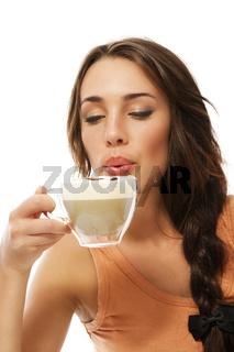 schöne frau pustet auf ihren heissen cappuccino kaffee