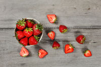 Tabletop view - small ceramic bowl of strawberries, more cut fruits lying around on gray wood desk.