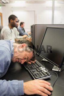 Man sleeping at the keyboard in computer class