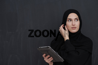 Young Arab businesswoman in traditional clothes or abaya holding tablet computer