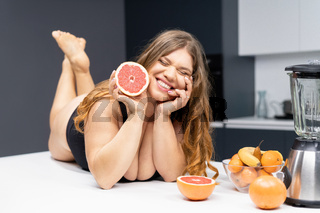 Young sexy chubby white girl in black swimsuit, white shirt at modern kitchen table. juggling fruits in hand. Trying to loose weight fast. Girl with obese problem. Fat barefoot girl low carb diet