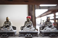Small bronze buddhist statues with coin and hat offerings in Daisho-in temple in Miyajima, Hiroshima