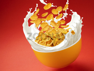 Corn flakes with milk splashes on red background
