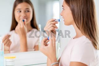teenage girl applying lip balm at bathroom