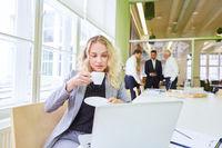 Geschäftsfrau am Computer trinkt eine Tasse Kaffee