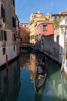 gondola with tourists travelling through the narrow canals of the old town of Venice