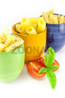 Fusilli, rigatoni and pens pasta in a green, blue and orange jar with tomatoes and basil