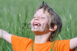 happy smiling child arms outstretched eyes closed enjoying the summer sun